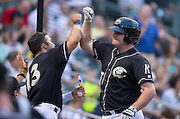 Dan Black (27) of the Charlotte Knights bumps forearms with teammate Carlos Sanchez (13) after hitting a 3-run home run against the Louisville Bats at BB&T BallPark on May 12, 2015 in Charlotte, North Carolina.  The Knights defeated the Bats 4-0.  (Brian Westerholt/Four Seam Images)