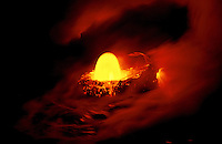 A dome of bright yellow fiery lava rises from a swirl of red molten lava from Kilauea volcano on the island of Hawaii.