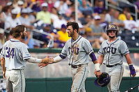 TCU Horned Frogs outfielder Dane Steinhagen (10) is greeted by teammate Garrett Crain (34) after scoring against the LSU Tigers in the NCAA College World Series on June 14, 2015 at TD Ameritrade Park in Omaha, Nebraska. TCU defeated LSU 10-3. (Andrew Woolley/Four Seam Images)