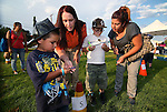 Amber Svensson, with CCSO Search and Rescue, helps D'Angelo Fillmore, 4, Tegan VanSickle, 7, and Maria Ramirez navigate the compass course at the 11th annual National Night Out hosted by the Carson City Sheriff's Office in Carson City, Nev., on Tuesday, Aug. 6, 2013. <br /> Photo by Cathleen Allison