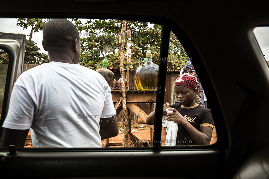 Vendita benzina , una ragazza prepara il filtro per versare la benzina Traffico illegale benzina dalla Nigeria al Benin