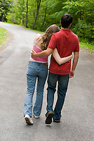 Young couple walking down country road