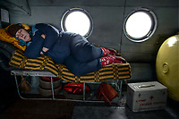 Paramedic Anna sleeps during a long helicopter flight to reach a patient. The vibrations during flights are harmful to the spine and are reduced if by lying in a horizontal position.
