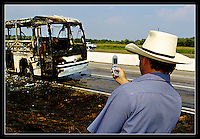 After leaving his truck idling on the frontage road, a curious passer-by, who refused to identify himself, snaps a camera-phone picture of a destroyed Mexican tour bus along southbound IH-35 near Salado, Texas on June 23, 2005.  The bus was in route to Celaya, Mexico when the rear tires caught fire and eventually caused a large explosion.  Fortunately, all of the passengers escaped to safety prior to the explosion. (Brian Ray for the Temple Daily Telegram)