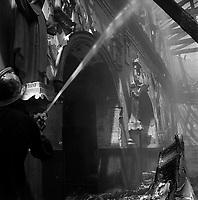 Eglise de Lalande, chemin de l'Eglise-de-Lalande. 20 juin 1961. Vue intérieure de l'église pendant l'incendie : au 1er plan pompier avec casque de dos tient une lance à eau ; en arrière-plan intérieur de l'église, toit détruit, décombres. Cliché pris pendant l'incendie qui a ravagé l'église de Lalande.