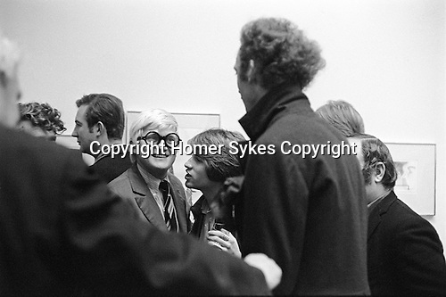 """Patrick Procktor and David Hockney. Hockney with his friend Peter Schlesinger whispering to him. RB Kitaj (extreme left just eyebrows showing, and Peter Blake right just half head behind PP.) Hockney opening night party at the  Kasmin Gallery 118 Bond Street London of """"Recent Etchings"""". 1969"""