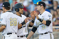Vanderbilt Commodores first baseman Zander Wiel (43) is greeted teammate Kyle Smith (39) after scoring against the TCU Horned Frogs in Game 12 of the NCAA College World Series on June 19, 2015 at TD Ameritrade Park in Omaha, Nebraska. The Commodores defeated TCU 7-1. (Andrew Woolley/Four Seam Images)