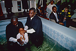 Church of God of Prophecy  In the church hall at Tubbs Road london the pastor and his assistant baptise a young boy. As in most 'born again' churches candidates make their own decision to be baptised by full immersion in the name of the Father , Son and Holy Ghost.