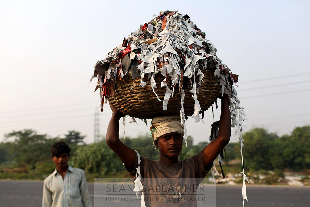 A man carries piles of leather trimmings that are to be burnt and used as fertilizer.<br />