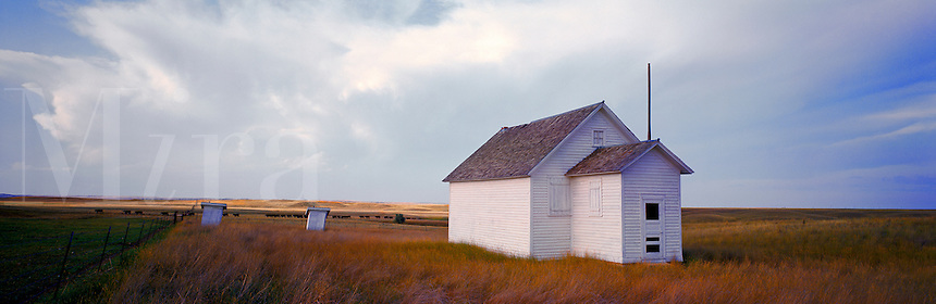 Panoramic view of an abandoned one room school house on an open prairie under a wide, cloudy sky with boys' and girls' outhouses in the distance. Montana.