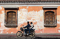 Antigua, Guatemala.  Couple on Motorcycle Ride Past Flaking Paint Revealing Age of an Old House.