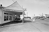 Y-680604-A21.  Stoner's Garage boasts gas priced at 30 cents per gallon. The garage was located on Highway 99E across the street from the funeral home and today is the Aurora Colony Auction House. Aurora, Oregon. June 4, 1968