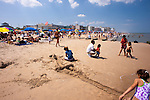 Children dig a canal in the sand, undisturbed by passing and nearby beachgoers on the first day of summer at Rehoboth Beach, Delaware, USA.