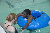 MR / Albany, NY.Langan School at Center for Disability Services .Ungraded private school which serves individuals with multiple disabilities.Teaching assistant holds hands and tries to encourage movement with non ambulatory student in swimming pool. Students in this class swim once a week as part of their physical education program. Girl: 10, African-American, cerebral palsy, expressive and receptive language delays.MR: And6; New1.© Ellen B. Senisi
