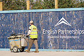 A street cleaner passes an English Partnerships sign on the site of the Greenwich Millenium Village, London.
