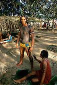 Altamira, Para State, Brazil. Kayapo woman applying body paint to Amauri, a warrior.