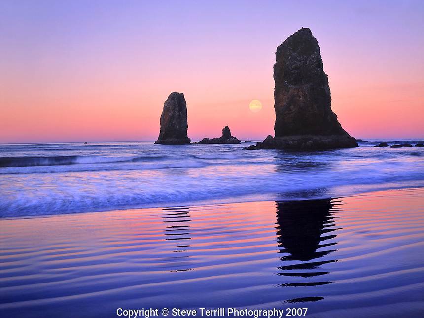The Needles rock monoliths at sunrise showing moon at moonset at Cannon Beach, Oregon