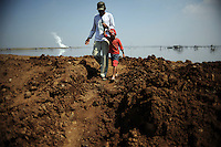 42 year old Fathoni, of Gempul Sari village, shows his five year old son the expanding lake of mud from vantage point of an earthen dam near their home. Since May 2006, more than 10,000 people in the Porong subdistrict of Sidoarjo have been displaced by hot mud flowing from a natural gas well that was being drilled by the oil company Lapindo Brantas. The torrent of mud - up to 125,000 cubic metres per day - continued to flow three years later.