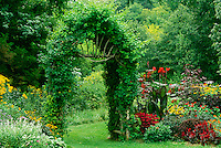Lush blooming garden is given a sense of extra space and privacy with handmade arbor using branches from trees, midwest USA
