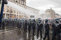 """Sogenannten """"Querdenker"""" sowie verschiedene rechte und rechtsextreme Gruppen hatten fuer den 18. November 2020 zu einer Blockade des Bundestag aufgerufen. Sie wollten damit verhindern, dass es eine Abstimmung ueber das Infektionsschutzgesetz gibt.<br /> Es sollen sich ca. 7.000 Menschen versammelt haben. Sie wurden durch Polizeiabsperrungen daran gehindert zum Reichstagsgebaeude zu gelangen. Sie versammelten sich daraufhin u.a. vor dem Brandenburger Tor.<br /> Im Bild: Die Polizei setzt nach Aufloesung der Kundgebung und mehrfachen Flaschenwuerfen vor dem Brandenburger Tor Wasserwerfer ein. Etliche Demonstranten waren mit entsprechender Schutzkleidung (Schutzbrillen und Regenkleidung) darauf vorbereitet. <br /> 18.11.2020, Berlin<br /> Copyright: Christian-Ditsch.de"""