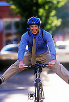 Happy businessman commutes to work by bicycle.