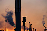 Smoking chimneys of a petroleum refinery at sunset, Berre, France.