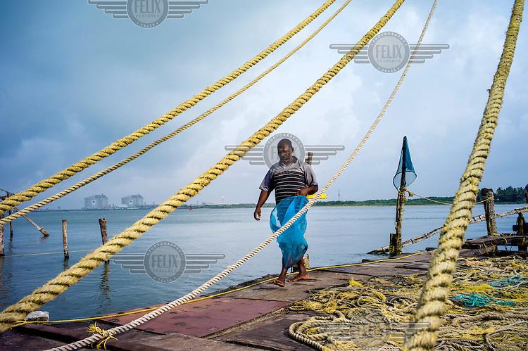 A fisherman walks on a jetty near Fort Kochi.
