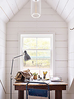The upstairs loft houses the white, wood panelled master bedroom. The room is light and airy with its vaulted ceiling and the simple blue and white theme gives the space a cool feel. A small writing desk set in a window recess provides a workspace.