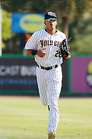"""Charleston Riverdogs outfielder Leonardo Molina (20) running into the dugout during a game against the Hickory Crawdads at the Joseph P. Riley Ballpark in Charleston, South Carolina. For Sunday games, the Riverdogs wear their """"Holy City"""" uniforms in honor of the city's nickname. Hickory defeated Charleston 8-7. (Robert Gurganus/Four Seam Images)"""
