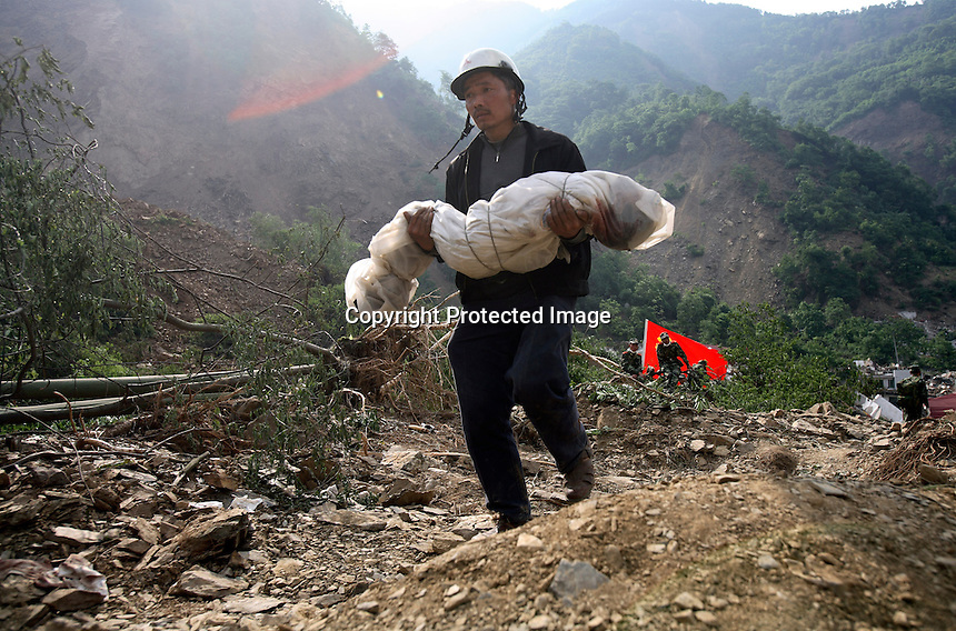A man carries the body of his son, a third grader, that he recovered from the ruins of a collapsed school complex in Beichuan, Sichuan, China. China now estimates the death toll to be around 50,000 as prospects of survival for those still buried diminishes..15 May 2008