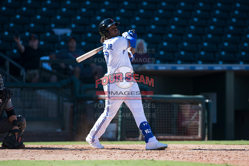 Surprise Saguaros third baseman Vladimir Guerrero Jr. (27), of the Toronto Blue Jays organization, follows through on his swing during an Arizona Fall League game against the Salt River Rafters on October 9, 2018 at Surprise Stadium in Surprise, Arizona. The Rafters defeated the Saguaros 10-8. (Zachary Lucy/Four Seam Images)