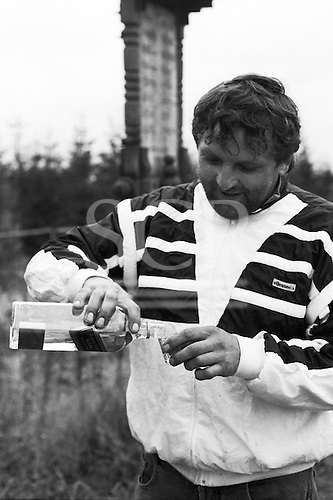 Ostrava, Czech Republic. Man pouring alcohol from Johnny Walker bottle in forest setting.