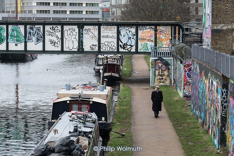A man walks on the towpath of the River Lee Navigation, part of the  London Capital Ring footpath, in Hackney Wick.
