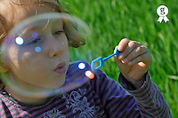 Girl (7-8) blowing bubbles by green field (Licence this image exclusively with Getty: http://www.gettyimages.com/detail/81867371 )