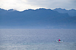 A lone fisherman dressed in pink on the water with mountains in the background as seen from Gili Trawangan, Lombok, Indonesia.