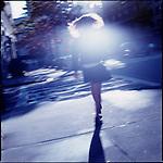 Schoolgirl walking down street away from camera
