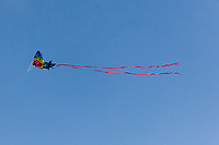 A butterfly shaped kite floats against a clear blue sky.
