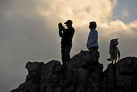 Silhouette of a man taking photograph of a landscape standing on a rock with wife and dog, at sunset, Hermanus, South Western Cape, South Africa