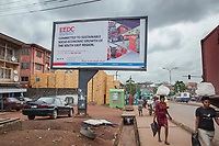 Nigeria. Enugu State. Enugu. Town center.  Igbo woman walk on the side walk and carry on their heads plastic bags filled with goods. A giant billboard with a poster from Enugu Electricity Distribution PLC (EEDC) with the words: Committed to sustainable socio-economic growth of South East Region (every evenings, people have too use generators due to electricity shortages !). In the back, a late deposit of a  retail dealer selling alcoholic beverages. 10.07.19 © 2019 Didier Ruef