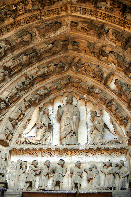 """South Porch, left Portal, Tympanum- General View.This portal is dedicated to the Confessors. Cathedral of Chartres, France. The tympanum, lintel and lower archivolts contain depictions of episodes in the martyrdom of Stephen. Christ between two kneeling angels. This is usually identified as the vision that Stephen saw during his martyrdom. Stephen saw Christ """"standing at the right hand of God"""", and in this depiction, Christ is standing. .Lintel: Stephen led to his martyrdom (left) and the Stoning of Stephen (right). Archivolts: .Lowest register - More incidents in the Martyrdom of Stephen. A UNESCO World Heritage Site. .."""