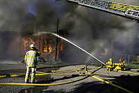 1992 File Photo Montreal (Quebec) CANADA<br /> Firemen create a a rainbow while directing  the water jet toward a burning old factory buiding,  No model release<br /> Photo (c) P Roussel / Images Distribution