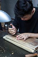 Yangzhou, Jiangsu, China.  China Block Printing Museum.  Calligrapher Carving Chinese Characters into Wood Block.