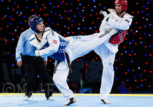 05 MAY 2012 - MANCHESTER, GBR - Aaron Cook (GBR) of Great Britain (left in blue) aims a kick at Ramin Azizov (right in red) of Azerbaijan during the men's 2012 European Taekwondo Championships -80kg final at Sportcity in Manchester, Great Britain (PHOTO (C) 2012 NIGEL FARROW)
