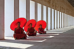 Myanmar, three monks sit with red umbrellas next to a colonnade