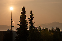 Smoke from wildifres makes for an orange sunrise and hazy mountains behind UAA's Consortium Library.
