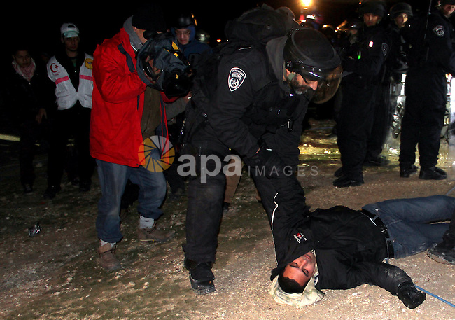 Israeli border police evict a Palestinian protester, from the scene in the controversial West Bank area known as E1 between Israeli annexed east Jerusalem and the settlement of Maaleh Adumim early on January 13, 2013. Israeli police early on January 13 evicted Palestinian protesters from a hilltop camp they set up in a West Bank area slated for Jewish settlement, police and witnesses said. Photo by Issam Rimawi