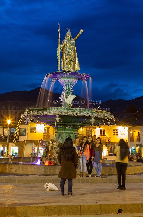 Peru, Cusco.  Plaza de Armas at Night.  Young Women Taking Photos.