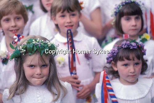 Castleton Garland Day Castleton Derbyshire UK May 29th. Schoolchildren taking party in parade. Flowers in hair. 1980s.