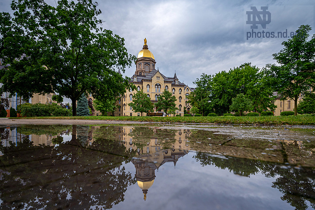 June 21, 2020; Main Building reflected in a puddle (Photo by Matt Cashore/University of Notre Dame)