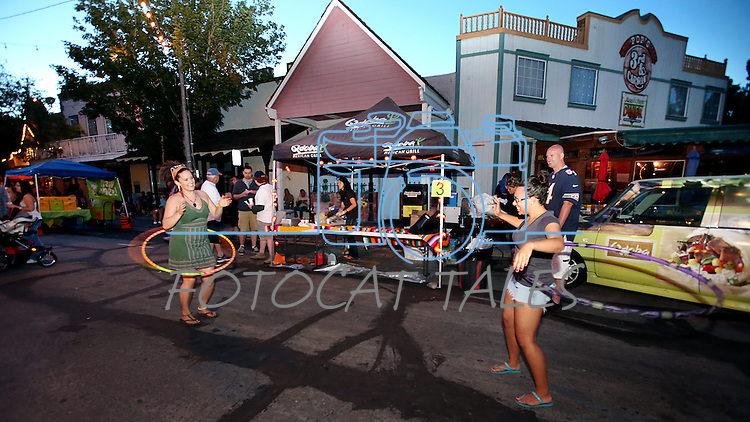 Dana Gaworski, left, and Chyna Metz play with hula hoops near the Qdoba booth at the 20th annual Taste of Downtown event in Carson City, Nev., on Saturday, June 15, 2013. The event features 44 local restaurants in a fundraiser for the Advocates to End Domestic Violence.<br /> Photo by Cathleen Allison